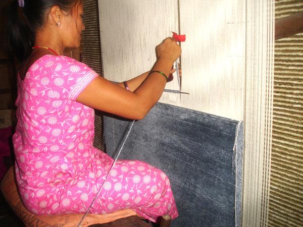 Woman knotting rug